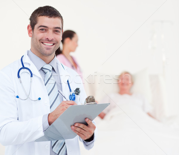 Confident chief physician in a hospital writing on a clip board Stock photo © wavebreak_media