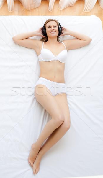 Erotische vrouw luisteren naar muziek bed muziek home Stockfoto © wavebreak_media