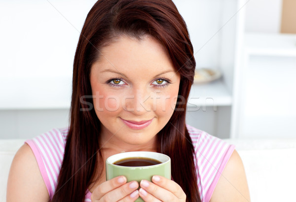 Portrait of an attractive woman holding a cup of coffee at home looking at the camera Stock photo © wavebreak_media