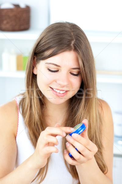Pretty woman using cream in the bathroom at home Stock photo © wavebreak_media