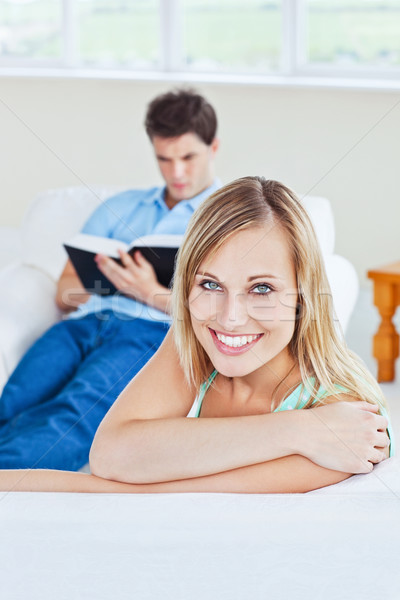 Girlfriend smiling at the camera while her boyfriend is focused on a  book sitting in the background Stock photo © wavebreak_media