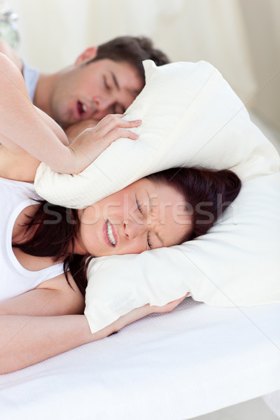 Young woman disturbed by the snores of her boyfriend in the bedroom at home Stock photo © wavebreak_media