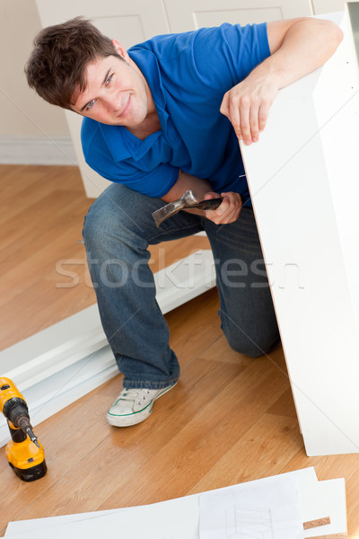 Smiling man assembling furniture and holding a hammer at home Stock photo © wavebreak_media