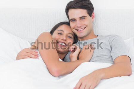 Man hugging his girlfriend on their bed at home Stock photo © wavebreak_media