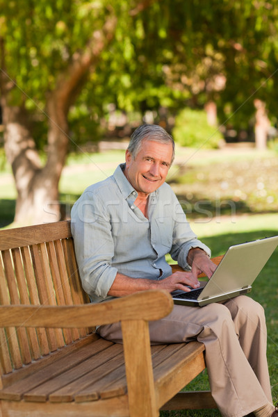 Elderly man working on his laptop in the park Stock photo © wavebreak_media