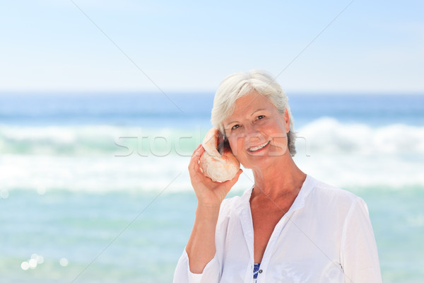 érett nő hallgat kagyló nő tengerpart lány Stock fotó © wavebreak_media