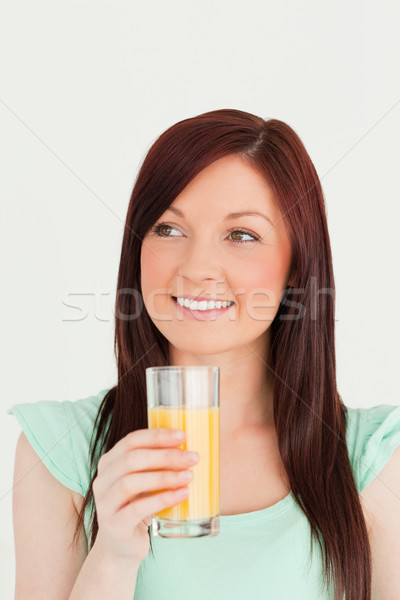 Glad red-haired woman enjoying a glass of orange juice in the kitchen in her appartment Stock photo © wavebreak_media