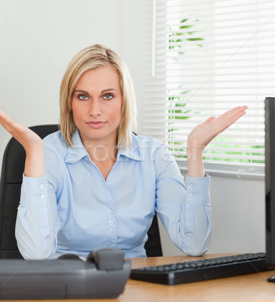 Serious woman sitting behind desk not having a clue what to do next in an office Stock photo © wavebreak_media