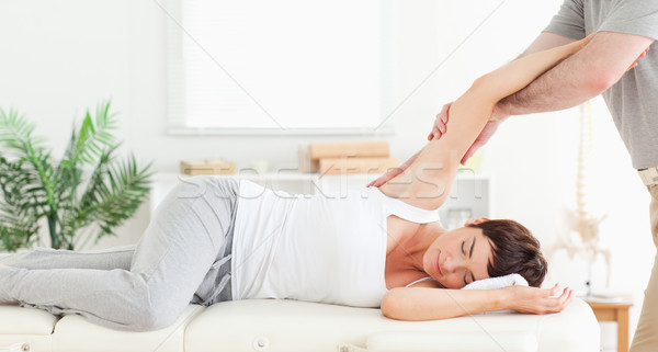 A chiropractor is stretching a woman's arm Stock photo © wavebreak_media