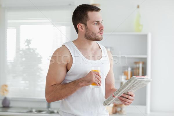Genç içme portakal suyu okuma haber mutfak Stok fotoğraf © wavebreak_media