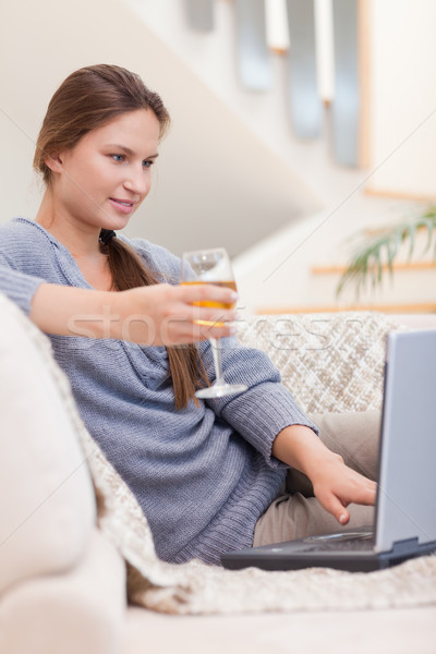 Stock photo: Portrait of a woman having a glass of white wine while using her laptop in her living room