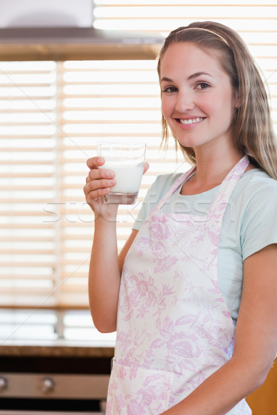 Stock photo: Portrait of a young woman drinking milk in her kitchen