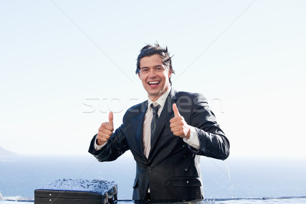 Businessman with the thumbs up in a swimming pool Stock photo © wavebreak_media