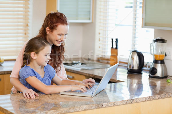 Mother and daughter together with laptop in the kitchen Stock photo © wavebreak_media