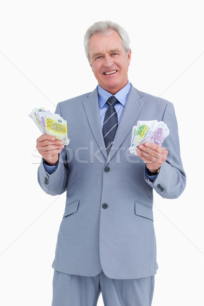 Smiling mature tradesman with cash in his hands against a white background Stock photo © wavebreak_media