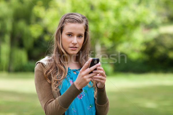 Teenager sending a text while standing in a park and looking at the camera Stock photo © wavebreak_media