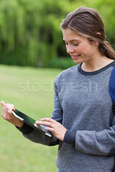Young happy woman smiling while touching her tablet pc and standing in a park Stock photo © wavebreak_media