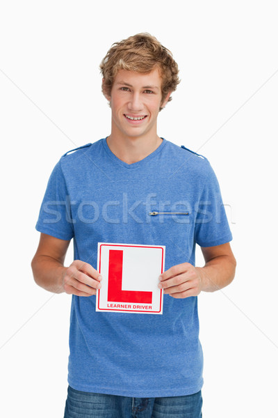 Young blond man holding a learner driver sign against white background Stock photo © wavebreak_media