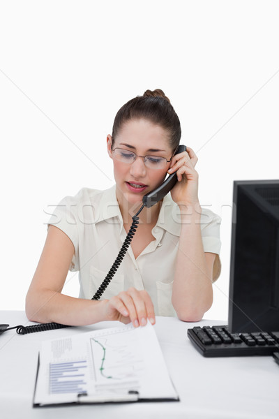 Portrait of a businesswoman making a phone call while looking at a document against a white backgrou Stock photo © wavebreak_media