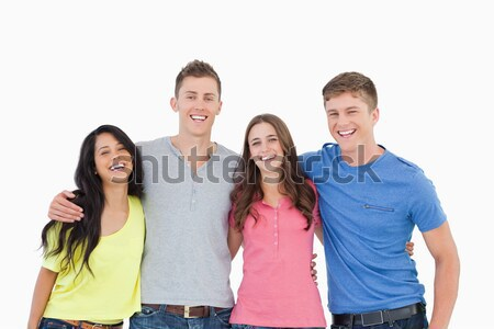 A laughing bunch of friends standing and holding each other as they all look into the camera  Stock photo © wavebreak_media