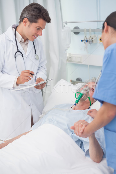 Doctor looking at patient next to a nurse in hospital ward Stock photo © wavebreak_media