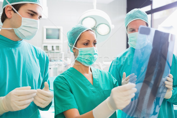 Surgical team looking at a X-ray in an operating theatre Stock photo © wavebreak_media