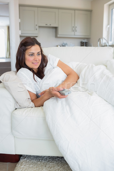 Woman lying on the couch while watching television in the living room Stock photo © wavebreak_media