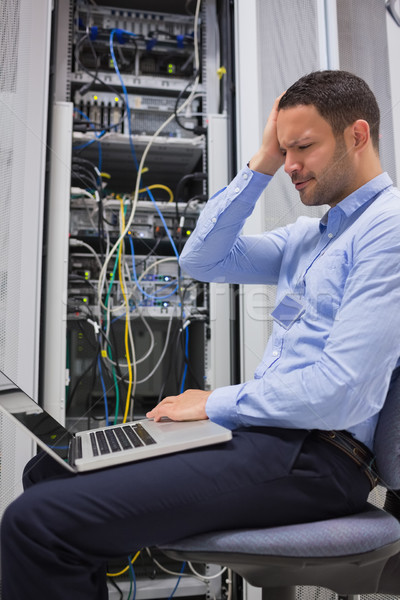 Worker looking stressed with laptop in data center Stock photo © wavebreak_media