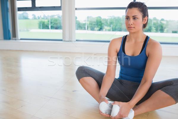 Woman doing bound angle yoga pose in fitness studio Stock photo © wavebreak_media