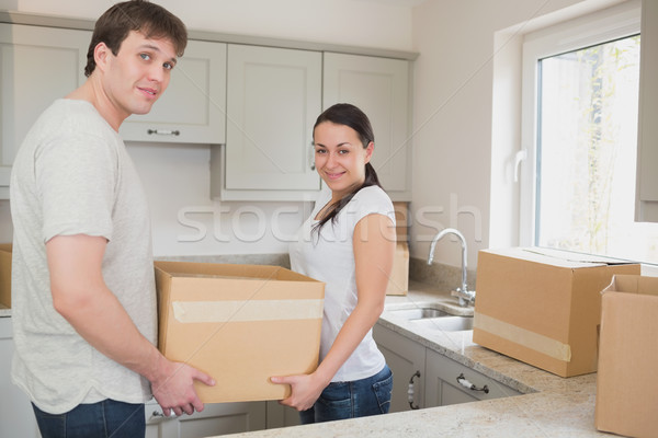 Young couple in the kitchen holding moving boxes and smiling Stock photo © wavebreak_media