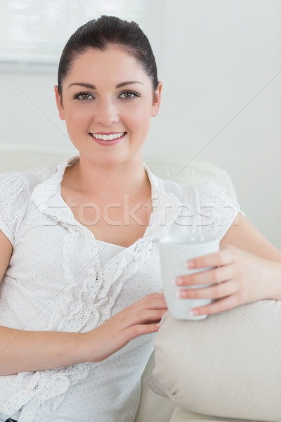 Happy woman holding a cup while sitting on a couch in a living room and relaxing Stock photo © wavebreak_media