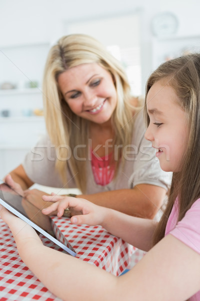 Stock photo: Woman and daughter holding a tablet pc while smiling at the kitchen table
