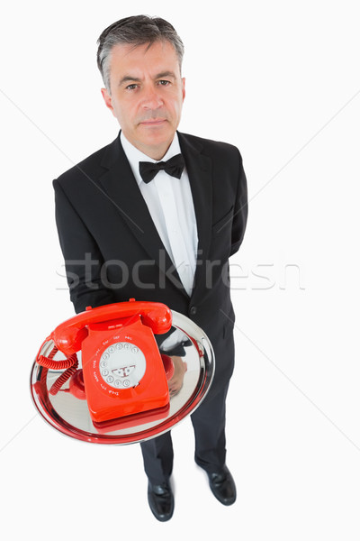 Waiter holding a red dial phone on a silver tray Stock photo © wavebreak_media