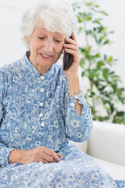 пожилого женщину мобильного телефона диван дома Сток-фото © wavebreak_media