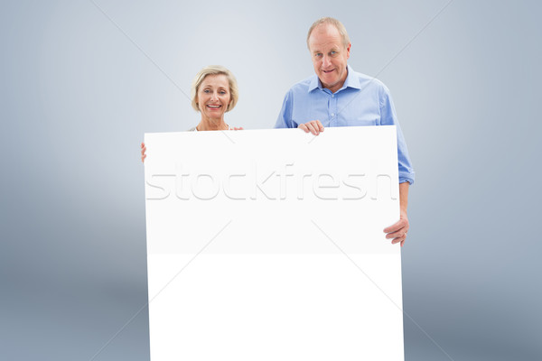 Composite image of mature couple smiling at camera holding card Stock photo © wavebreak_media