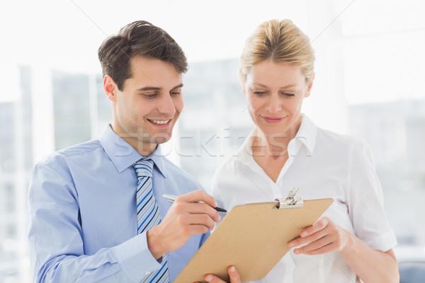 Uśmiechnięty zespół firmy patrząc schowek wraz biuro Zdjęcia stock © wavebreak_media