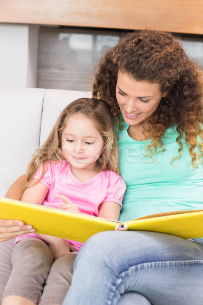 Pretty mother helping her little daughter read a storybook Stock photo © wavebreak_media