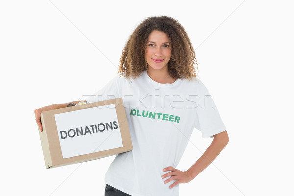 Happy volunteer holding a box of donations with hand on hip Stock photo © wavebreak_media