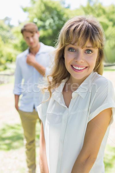 Beautiful blonde smiling at camera with boyfriend in background Stock photo © wavebreak_media