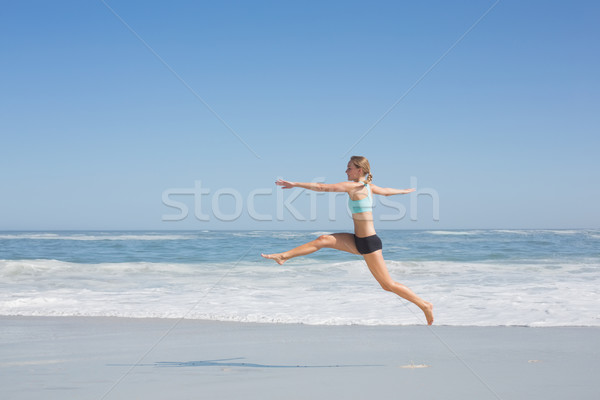 Fit woman jumping gracefully on the beach  Stock photo © wavebreak_media