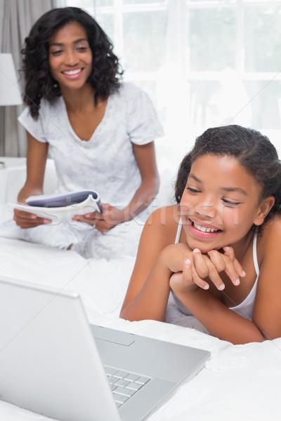 Moeder lezing magazine dochter met behulp van laptop bed Stockfoto © wavebreak_media