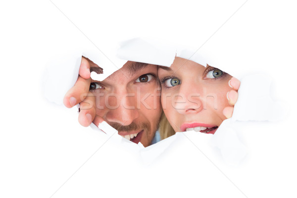 Young couple peeking through torn paper Stock photo © wavebreak_media