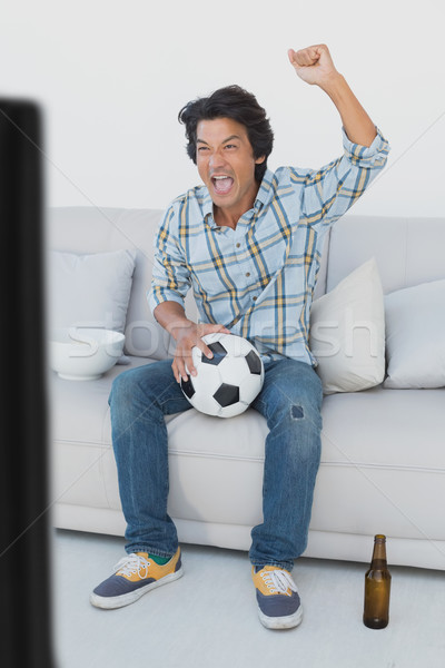 Soccer fan cheering while watching tv Stock photo © wavebreak_media