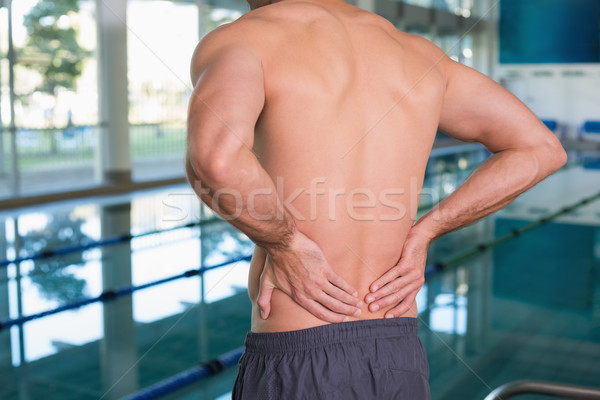 Mid section of shirtless fit swimmer with back ache by pool Stock photo © wavebreak_media