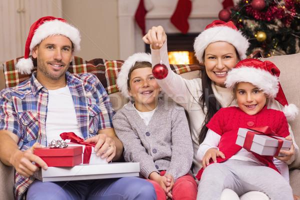 Happy family wearing santa hat on the couch Stock photo © wavebreak_media