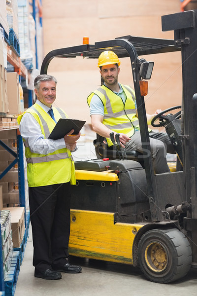 Driver operating forklift machine next to his manager Stock photo © wavebreak_media