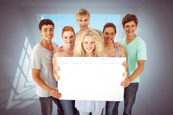 Composite image of group of teenagers holding a blank card Stock photo © wavebreak_media