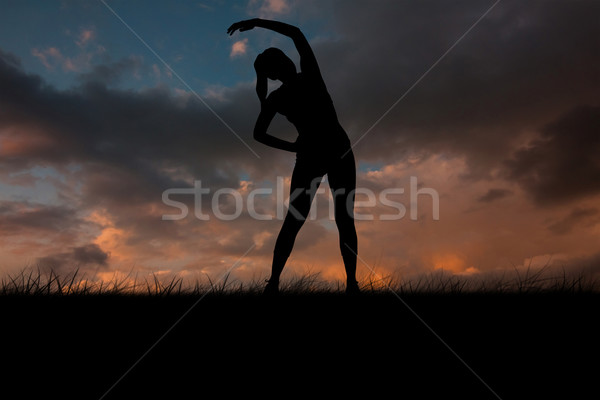Composite image of fit brunette stretching and smiling Stock photo © wavebreak_media