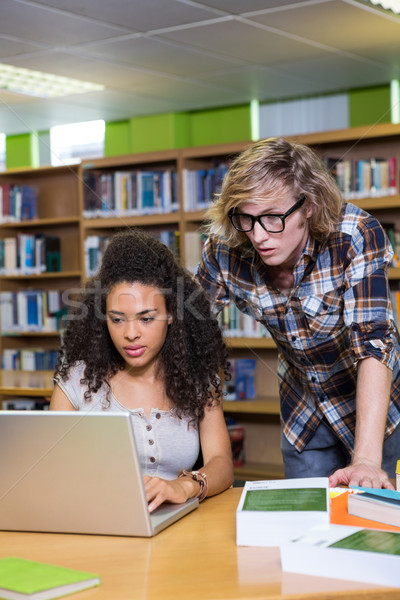 Student getting help from classmate in library Stock photo © wavebreak_media