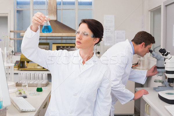 Scientists working with microscope and beaker  Stock photo © wavebreak_media